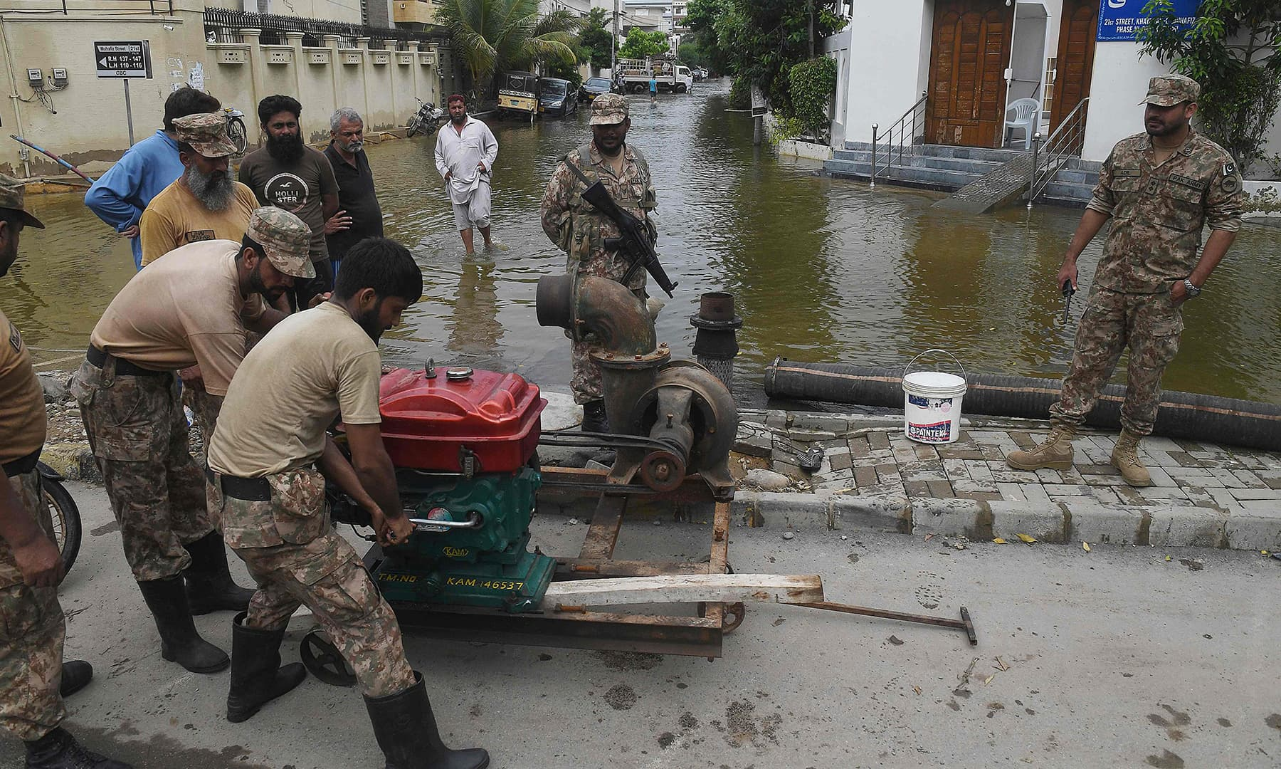 Troops install a water pump to remove water from a flooded residential area following heavy monsoon rains in Karachi on August 31. — AFP