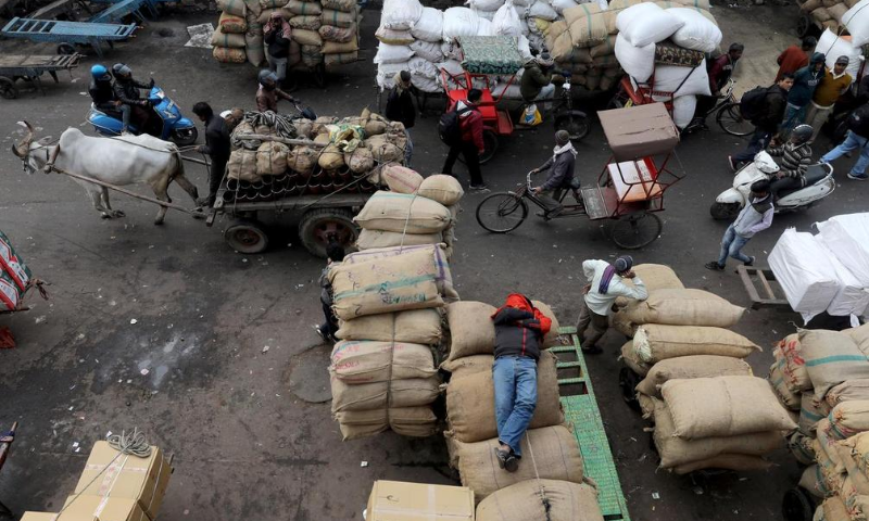 A labourer sleeps on sacks as traffic moves past him in a wholesale market in the old quarters of Delhi, India. — Reuters/File