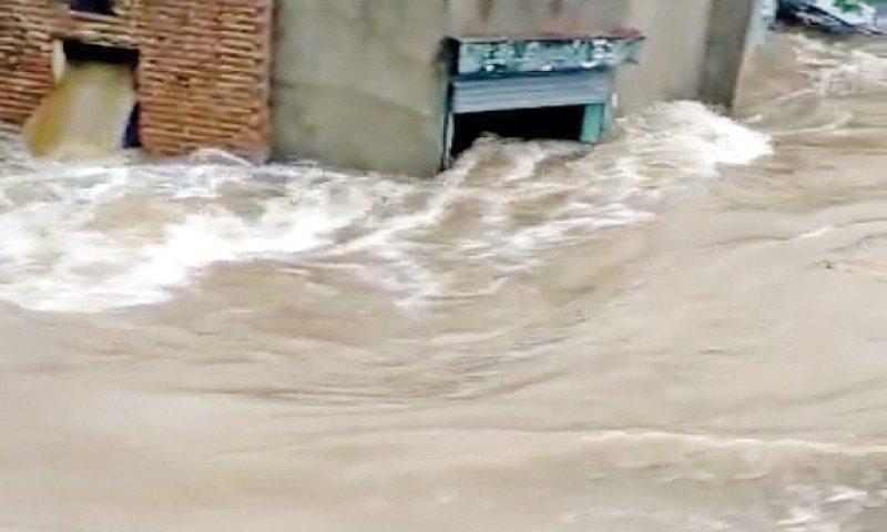 Shops in Nurpur village have been flooded following the rain. — Dawn