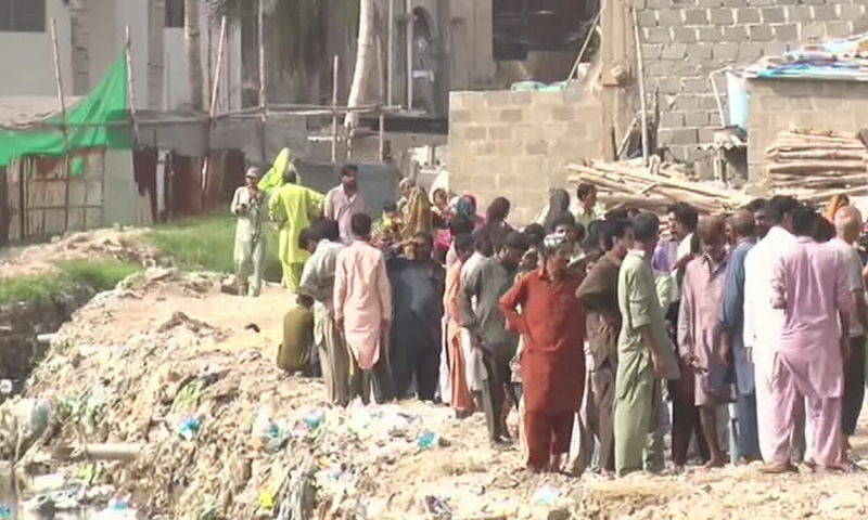 Residents living next to Gujjar Nala watch the anti-encroachment operation take place on Wednesday. — DawnNewsTV