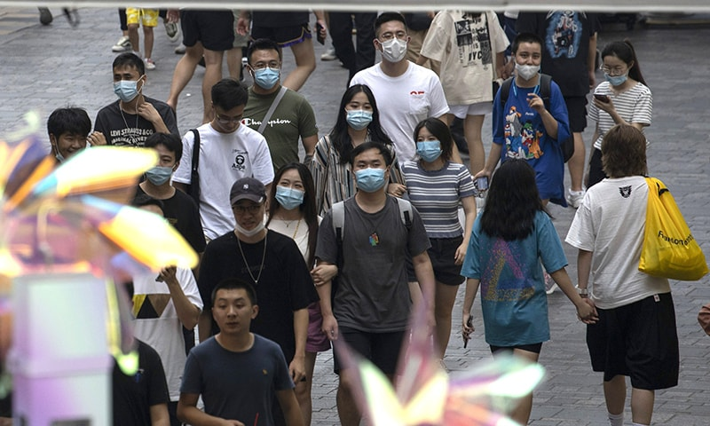 Shoppers wearing masks to curb the spread of the coronavirus walk through a mall district in Beijing on Sunday, Aug 30. — AP