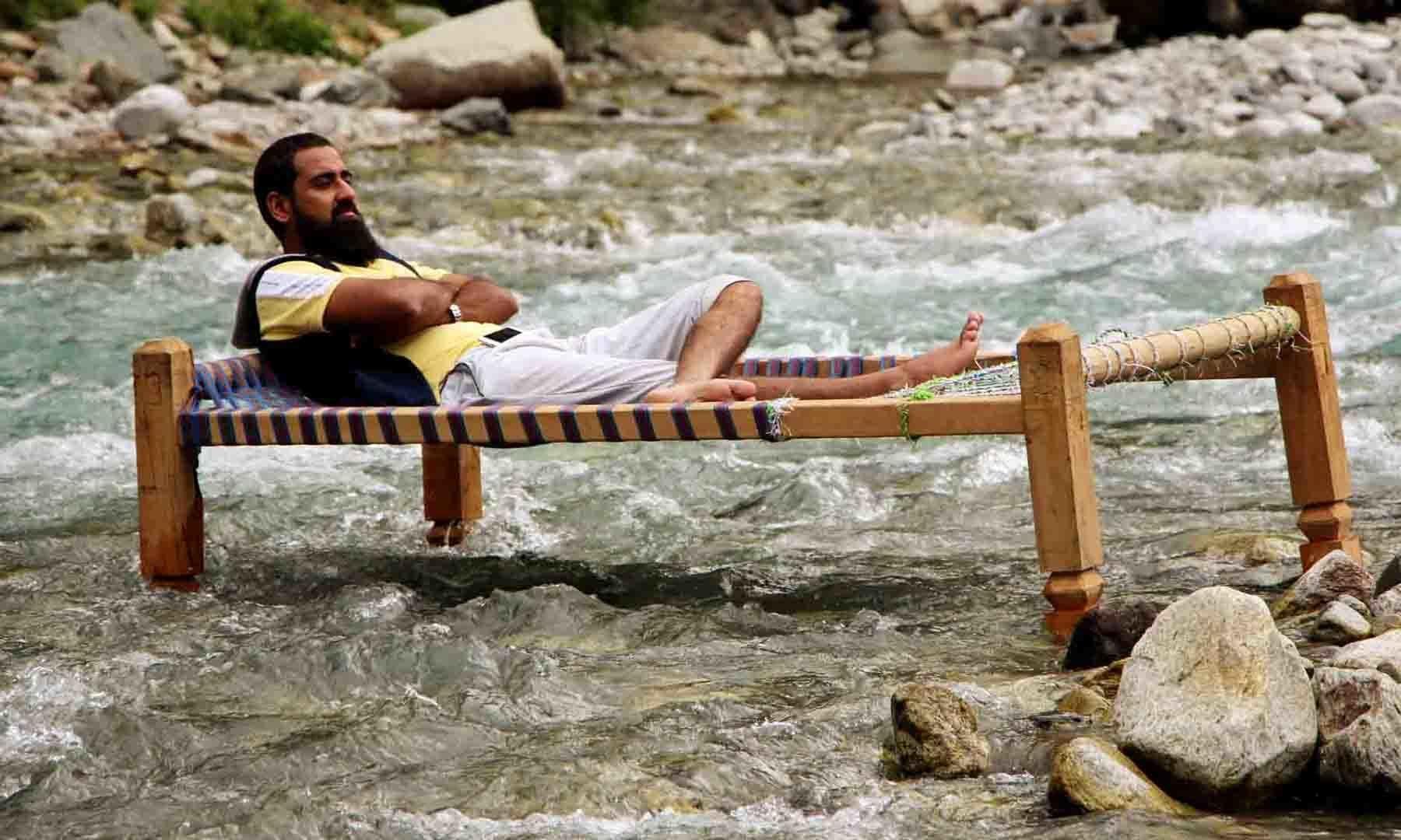 ایک سیاح دریائے سوات کے کنارے مشہور سیاحتی مقام بلیو واٹر میں سکون کے لمحات کشید کر رہا ہے—فوٹو: امجد علی سحاب