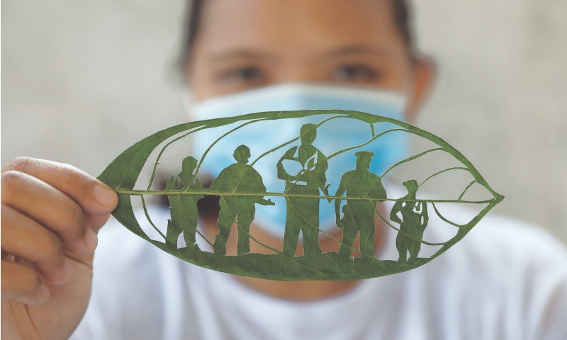 BINAN (Philippines): Filipino artist Mary Mae Dacanay shows one of her leaf artworks, a tribute to Covid-19 frontliners.—Reuters
