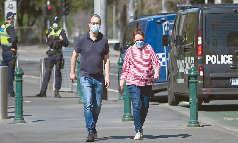 MELBOURNE: A couple takes a walk as police look on during a relaxation in lockdown restrictions on Sunday.—AFP