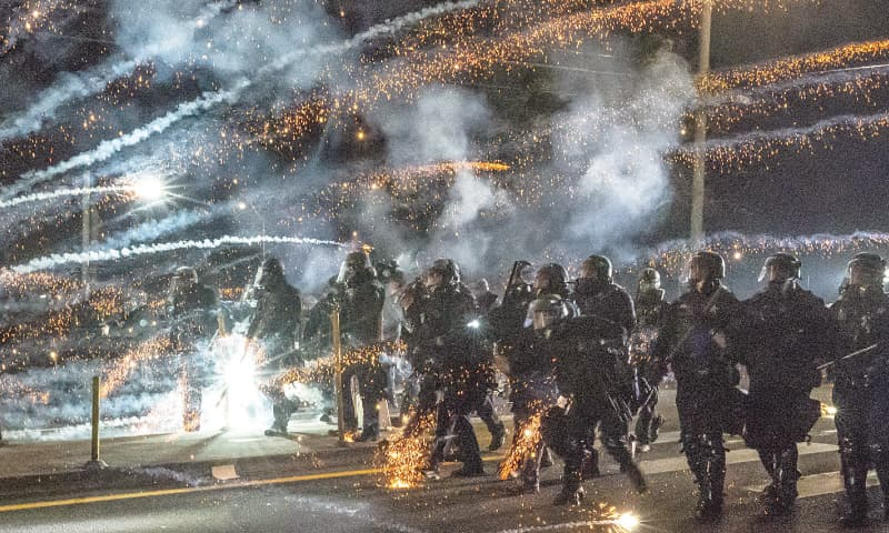 PORTLAND (Oregon, US): Soldiers and police advance through tear gas and fireworks while dispersing a protest against police brutality and racial injustice.—AFP
