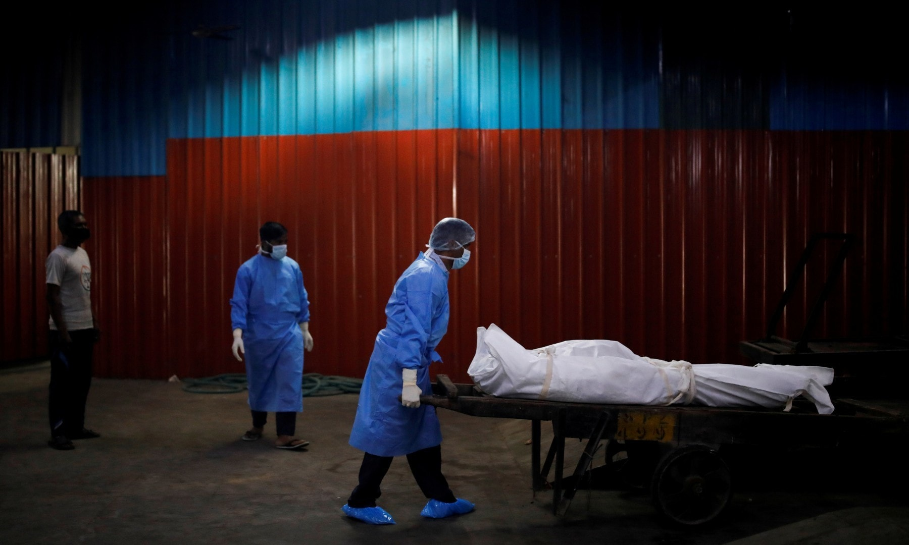 A health worker wearing personal protective equipment carries the body of a man, who died due to the coronavirus at a crematorium in New Delhi on September 7. — Reuters