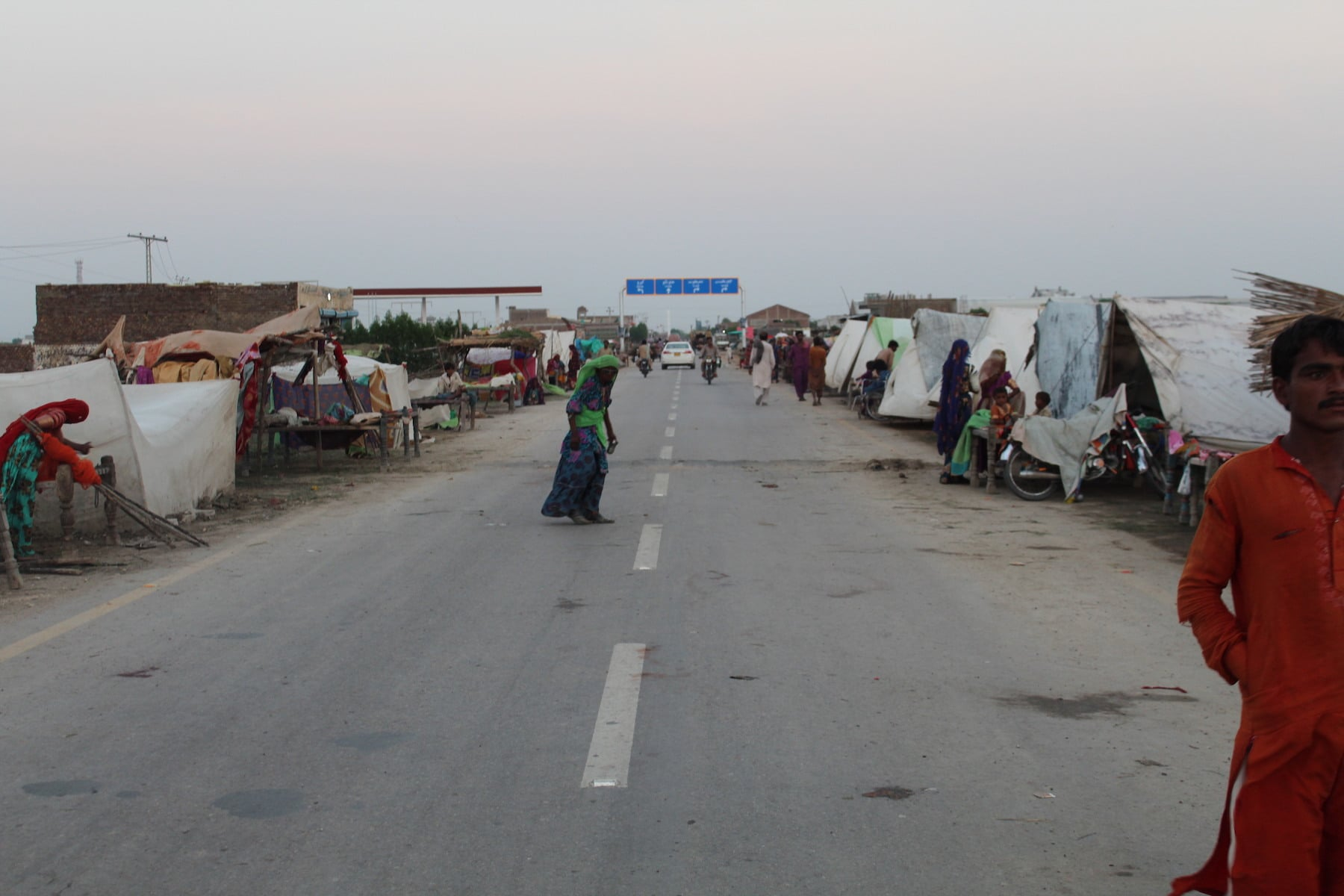 Villagers have set up make-shift tents on both sides of the road, which is higher than the lands surrounding it. Hundreds of thousands of people have been displaced in Mirpurkhas division in the aftermath of the torrential rains. — Photo by author