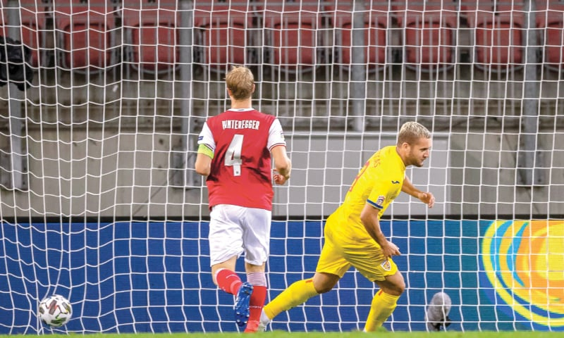 KLAGENFURT (Austria): Romania's George Puscas (R) scores during the match against Austria.—AFP