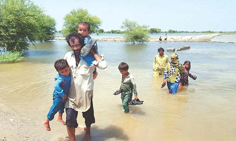 BADIN: Some families moving to safe places on Monday after their houses were submerged by floodwater. — PPI