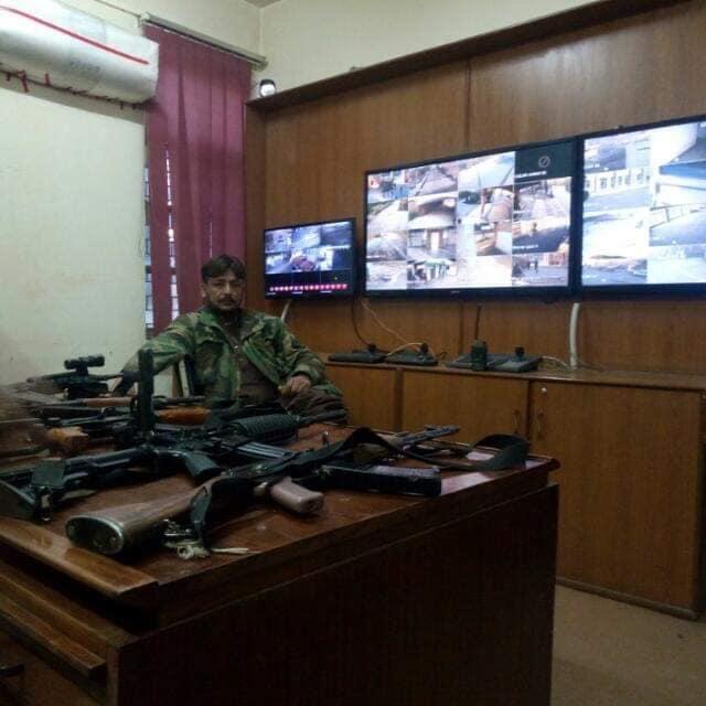 یو او بی کنٹرول روم میں سیف بلوچ اپنی میز پر مختلف بندوقوں کے ساتھ موجود ہے— فوٹو: بشکریہ ٹوئٹر