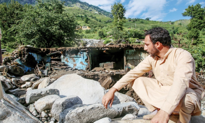 Gloomy Bakht Sherawan sitting in front of his destroyed house in Swat. — Dawn