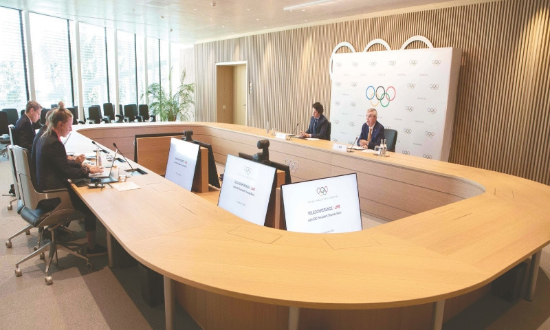 IOC president Thomas Bach (above R) holding a remote press conference following an executive board meeting at the IOC headquarters.—AFP