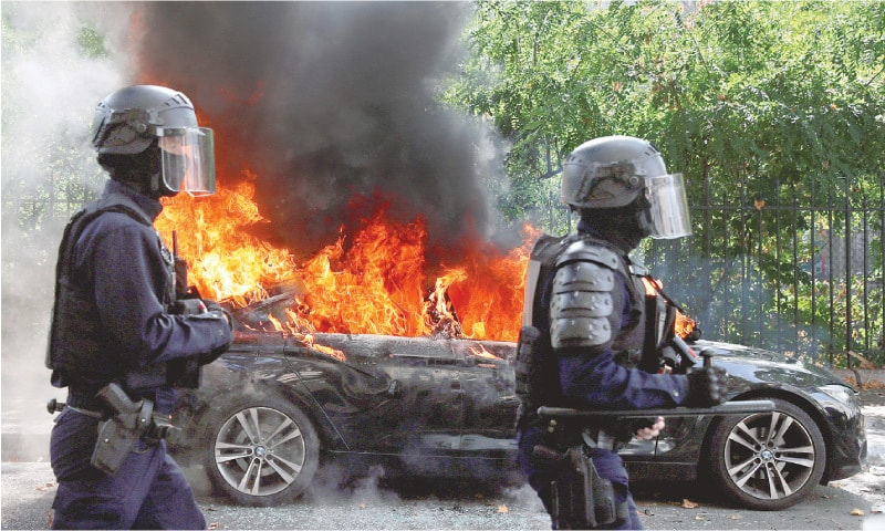 French riot police officers walk past a burning car during a demonstration of the yellow vests movement in Paris on Saturday.—Reuters