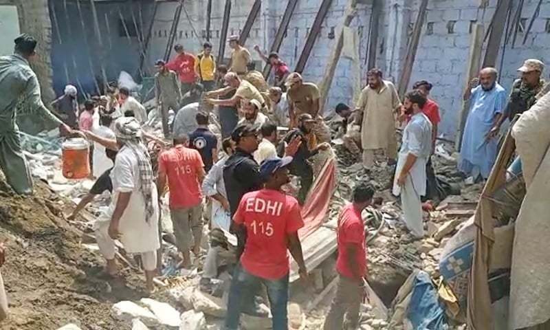 Rescue workers at the site of the building collapse. — DawnNewsTV