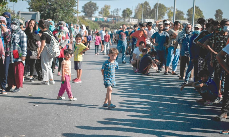 LESBOS (Greece): Children of asylum-seekers bide their time as adults queue for food distribution along the roadside following the burning down of their camp last week.—AFP