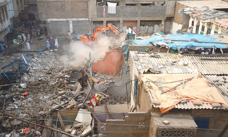 An excavator is removing the debris of the collapsed building in Lyari on Sunday.—Shakeel Adil/ White Star