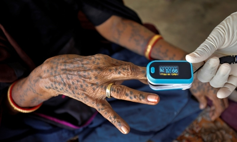 A healthcare worker puts a pulse oximeter on a woman's finger to check her oxygen level during a door-to-door survey in Moriya village on the outskirts of Ahmedabad on September 14. — Reuters