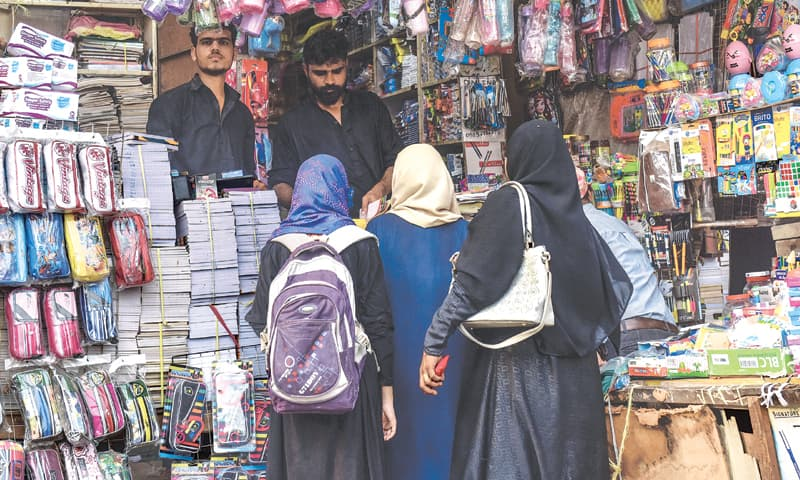 A family purchases school supplies from an Urdu Bazaar vendor on Monday.—Fahim Siddiqi/White Star