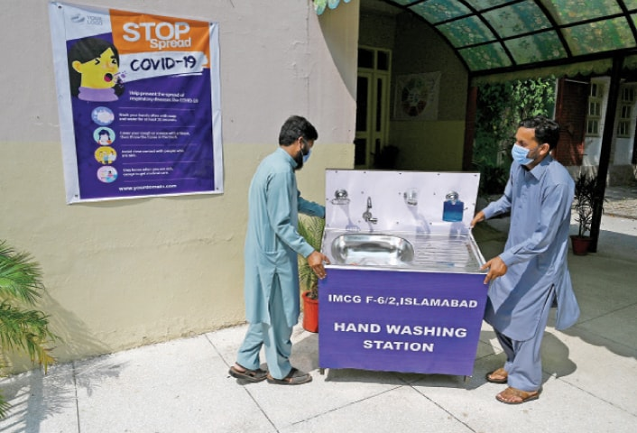 College staff place a handwashing station at the entrance of IMCG F-6/2 in Islamabad on Monday. Educational institutions reopen today (Sept 15), nearly six months after being closed due to the spread of Covid-19. — Photo by Mohammad Asim