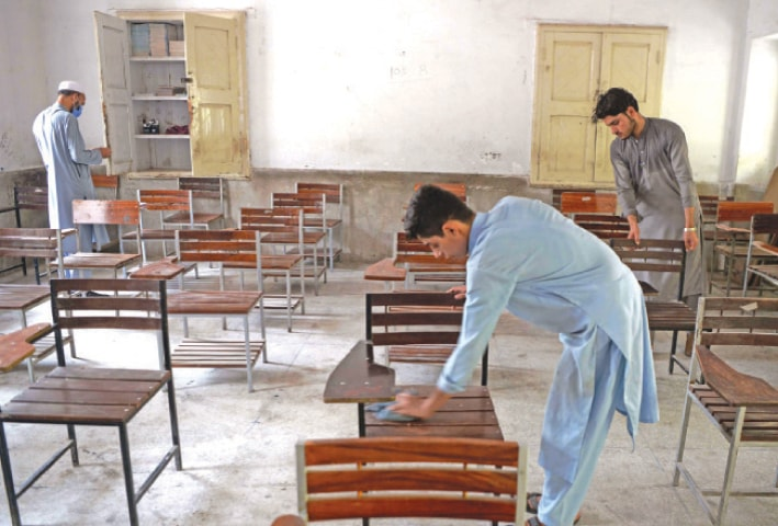 Workers clean a classroom of a government school in Peshawar on Monday. — White Star