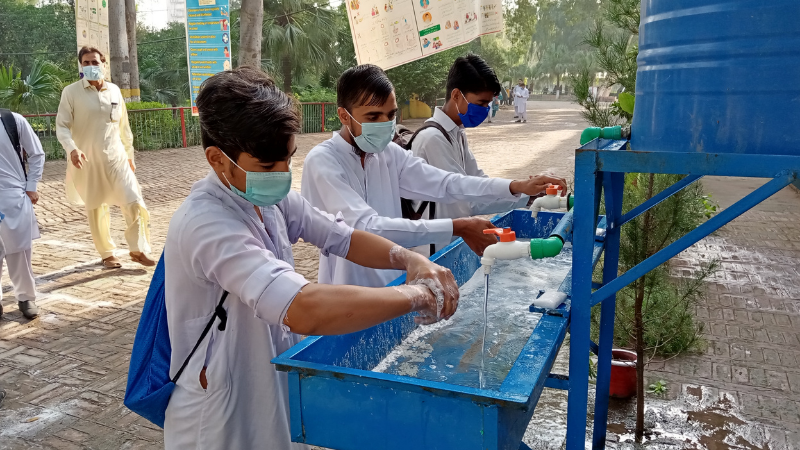 Students wash their hands before entering as schools reopen in Peshawar. — Photo by Sirajuddin