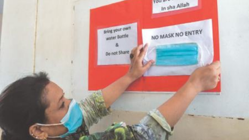 اسکول کے نوٹس بورڈ پر استاد ماسک کے بغیر داخلے پر پابندی کا سائن لگارہے ہیں ۔ فوٹو:اے ایف پی