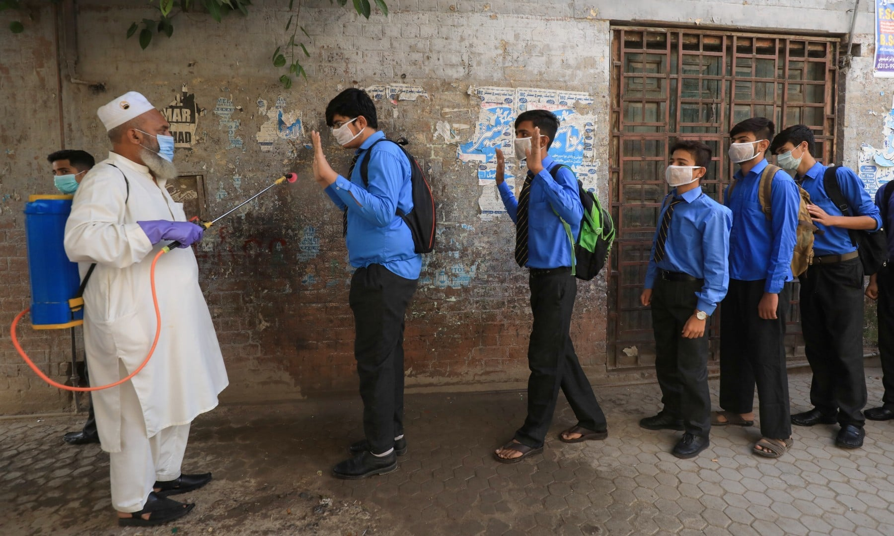 An employee disinfects students before they enter classes as schools reopen in Peshawar on September 15. — Reuters