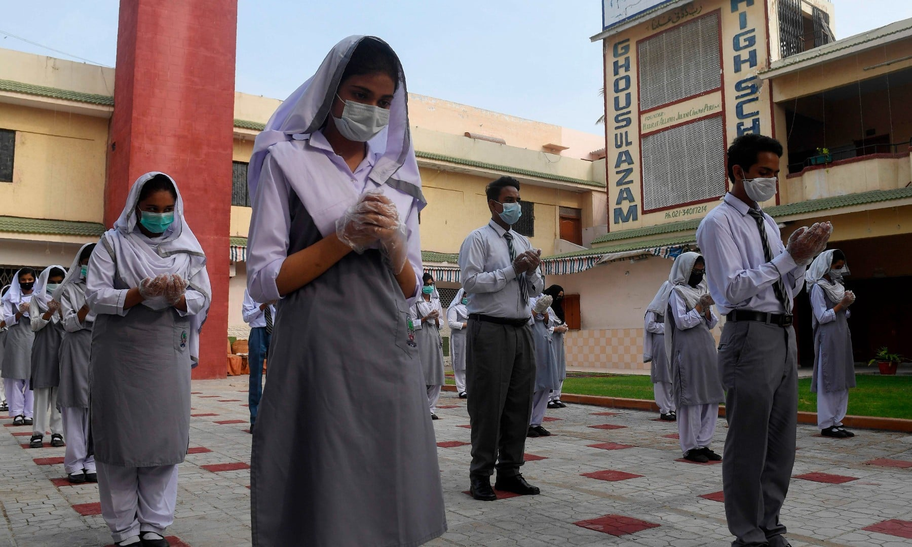 Students wearing face masks and gloves take part in an assembly at a school in Karachi on September 15. — AFP/File