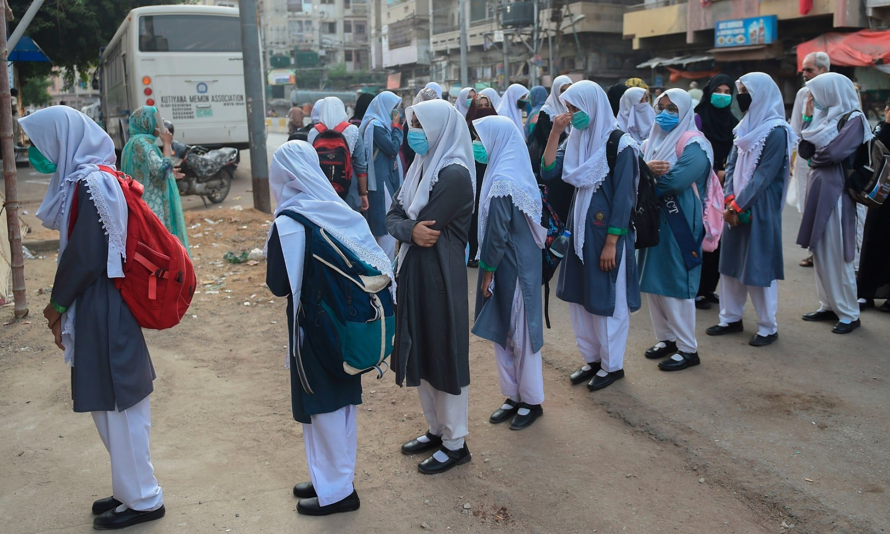 Students wearing face masks stand in queue as they wait to enter their school in Karachi on September 15. — AFP