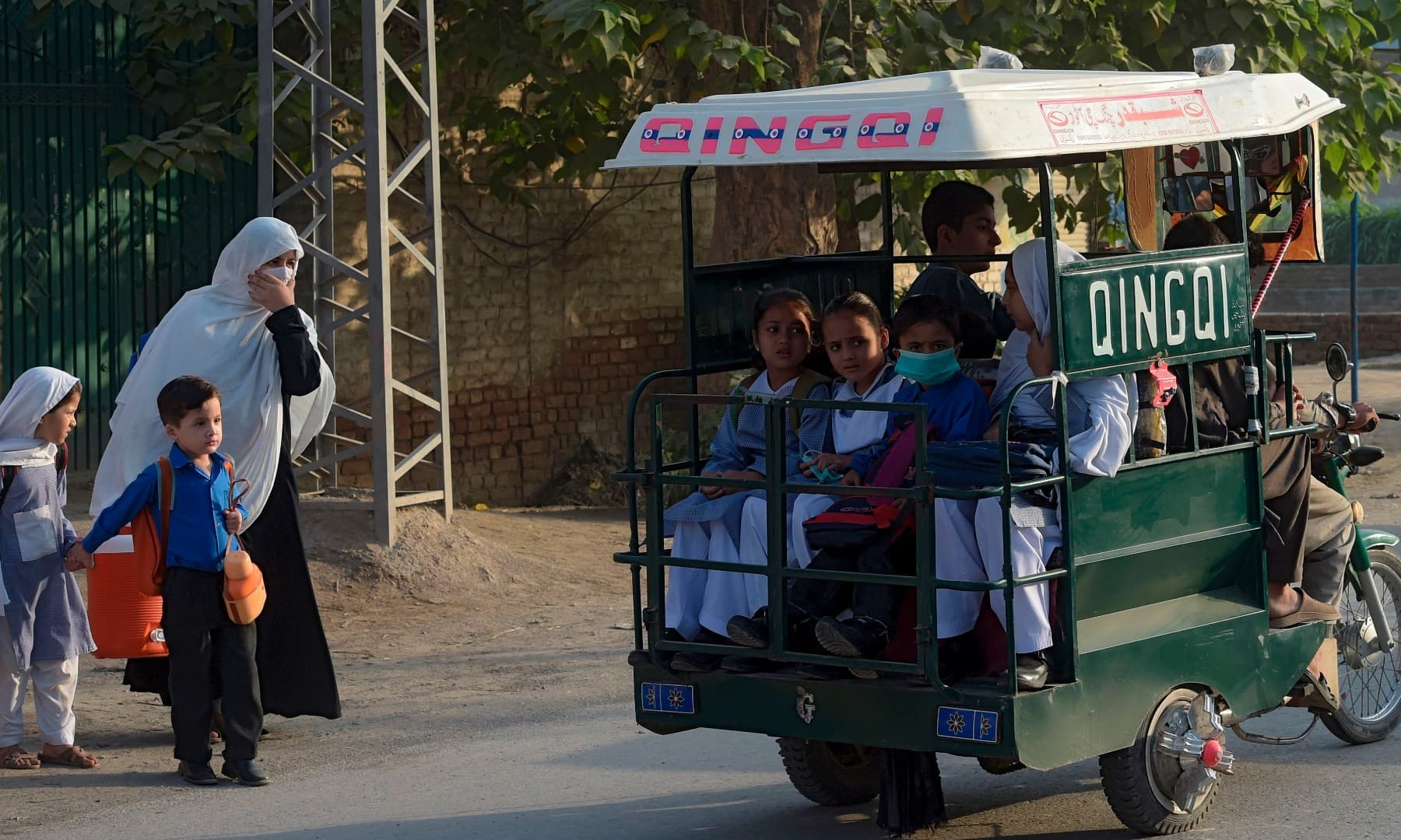 Students ride on a three-wheeler vehicle on way to their school in Peshawar on September 15. — AFP
