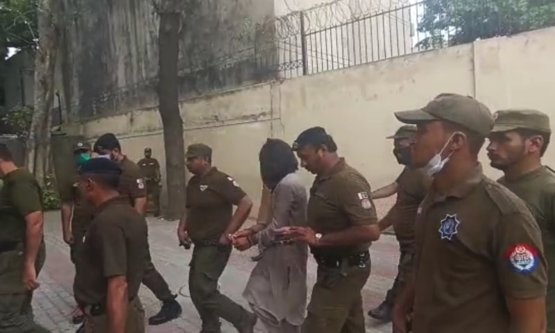 The suspect is escorted into the court by police on Tuesday. — DawnNewsTV