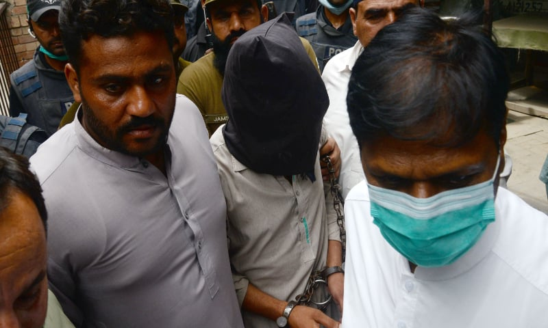 Policemen escort Shafqat Ali (face covered), one of two suspects in the motorway gang-rape case, as they leave from a local court in Lahore on September 15. — AFP