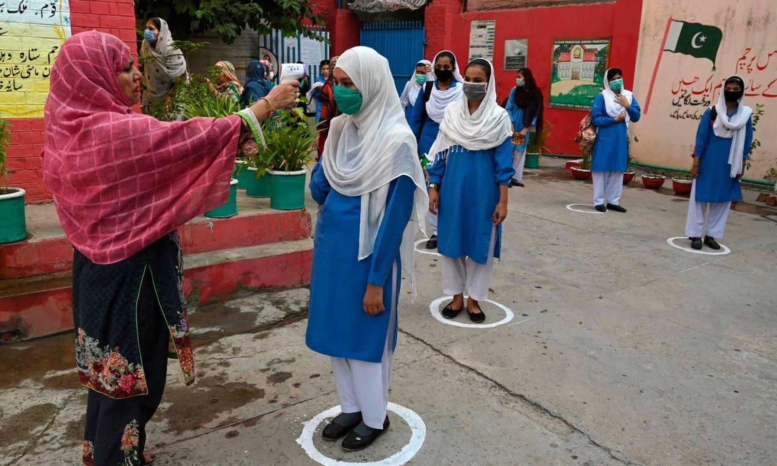 اسکولز میں داخلے کے وقت طلبہ کا درجہ حرارت چیک کیا گیا — فوٹو: اے ایف پی