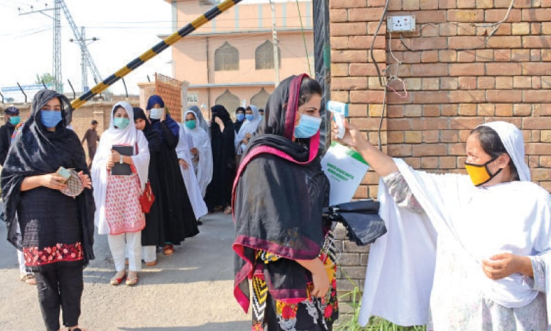 Temperature of students being checked on arrival at Shaheed Benazir Bhutto Women University, Peshawar, on Tuesday. — White Star