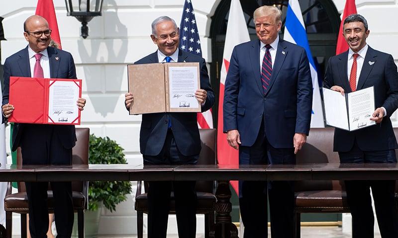 تینوں ملکوں کے نمائندے معاہدے پر دستخط کے بعد اسے دکھا رہے ہیں— فوٹو: اے ایف پی