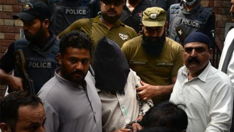 Police escort Shafqat Ali (face covered) as he leaves a court.