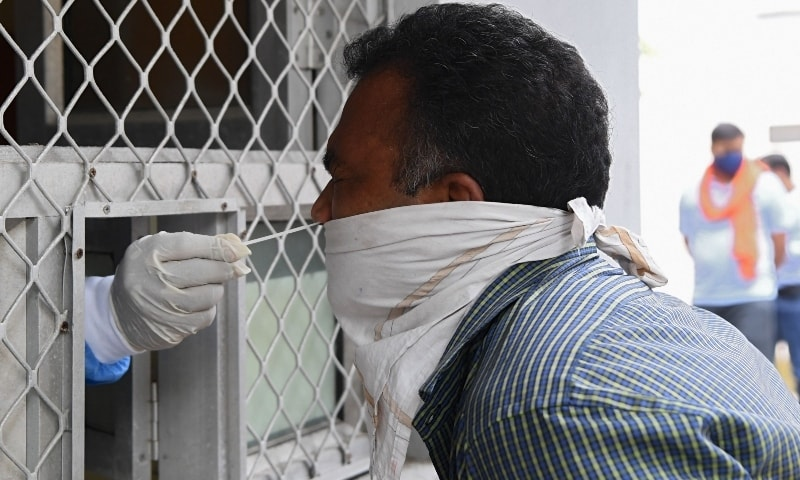 A medical worker collects a swab sample from a man for a Rapid Antigen Test at a government health center in New Delhi on September 16. — AFP