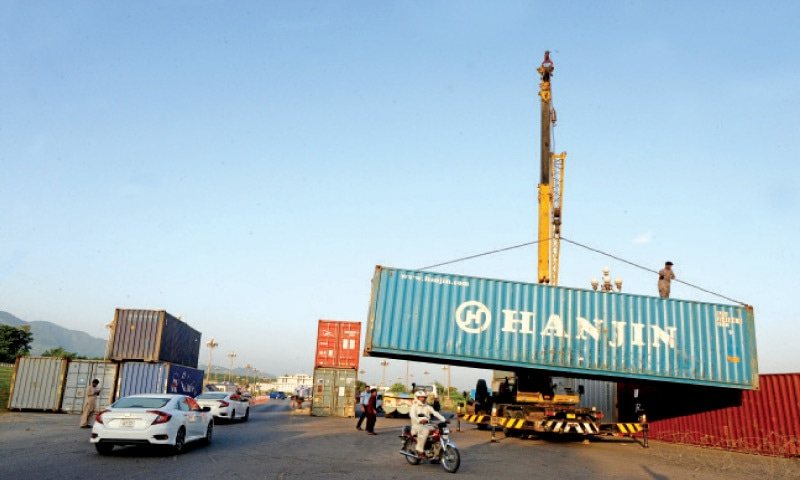 The district administration places containers at D-Chowk in Islamabad on Wednesday, ahead of the Muttahida Sunni Council procession on Thursday. — Photo by Mohammad Asim