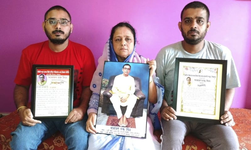 Anindita Mitra, 61, flanked by her sons Satyajit Mitra, right and Abhijit Mitra, pose with portraits of her husband late Narayan Mitra, at her house in Silchar, India, Sunday, Sept 13. — AP