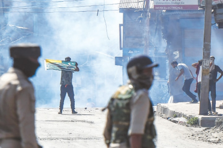 SRINAGAR: A protester waves a flag of Azad Jammu & Kashmir during clashes with Indian occupation forces here on Thursday. Hundreds of residents clashed with the Indian forces after a firefight left four people, including a young woman, dead.—AFP