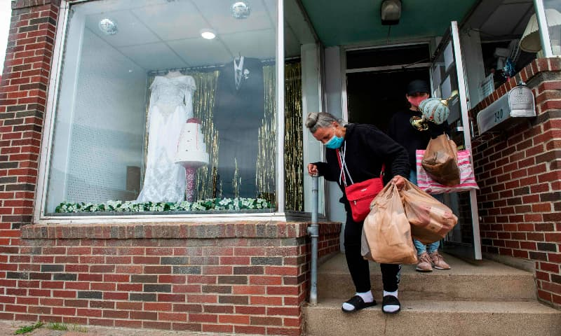 People wearing masks exit a thrift shop where a bridal gown and a groom tuxedo are displayed in the window in downtown Millinocket, Maine on September 17, 2020. — AFP