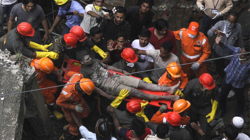 Rescue workers carry a survivor from the rubble of a collapsed three-storey residential building in Bhiwandi on Sept 21. — AFP