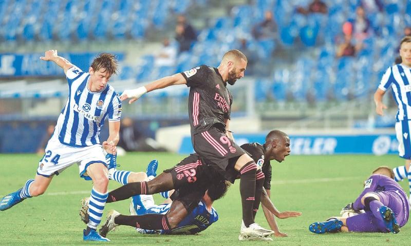 SEN SEABASTIAN: Real Madrid's Ferland Mendy (second R) falls beside team-mate Karim Benzema and Real Sociedad's Robin Le Normand (L) during their La Liga match at the Anoeta Stadium.—AFP