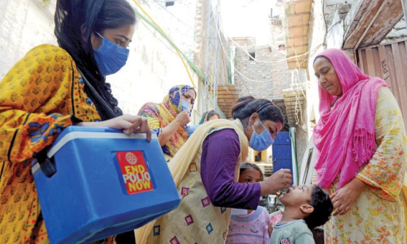 An MCI health worker administers the polio vaccine to a child in France Colony, in Islamabad's F-7 sector on Monday. — Mohammad Asim