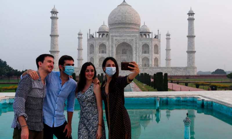 Tourists have their pictures taken at the Taj Mahal in Agra on Sept 21. — AFP
