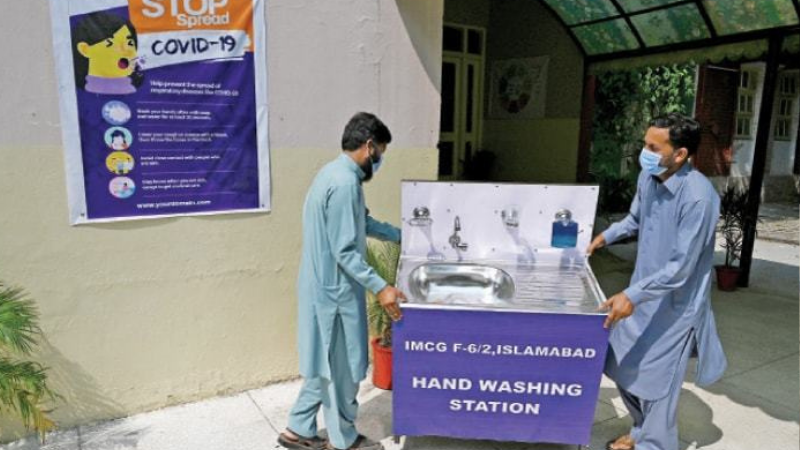 College staff place a handwashing station at the entrance. — Photo by Mohammad Asim/File