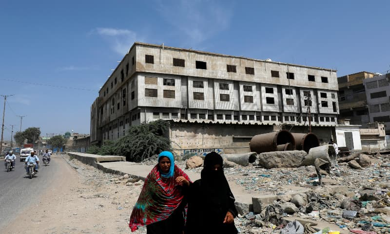 Women walk along a road with the abandoned building of the Baldia garment factory where the deadly fire occurred in the background, in Karachi, Sept 17, 2020.  — Reuters