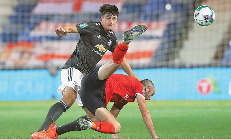 LUTON: Manchester United's Harry Maguire (L) fights for the ball with Luton Town's Danny Hylton during their English League Cup third-round match at Kenilworth Road.—AP