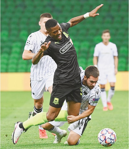 KRASNODAR: FC Krasnodar's Kaio vies for the ball with PAOK Salonika's Andrija Zivkovic (R) during the first leg of their Champions League playoff at the Krasnodar Stadium.—Reuters