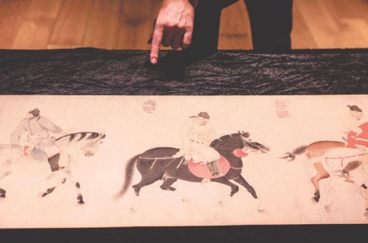 """HONG KONG: A scroll titled """"Five drunken princes returning on horseback"""" by Ren Renfa on display at Sotheby's on Wednesday.—AFP"""